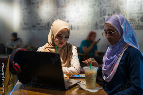 Fotografie, Obraz  Two happy women with coffee doing job and discussing with laptop in coffeeshop, indoor, selective focus
