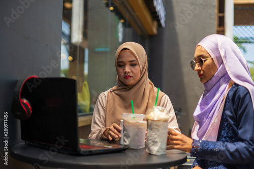 Fotografie, Obraz  two happy young Asian Muslim women in coffeehouse or coffee shop, discussing each other, leisure time with friends with laptop
