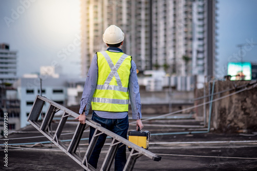 Vászonkép Asian maintenance worker man with safety helmet and green vest carrying aluminium step ladder and tool box at construction site