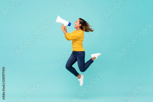 Girl with megaphone jumping and shouting Fototapeta