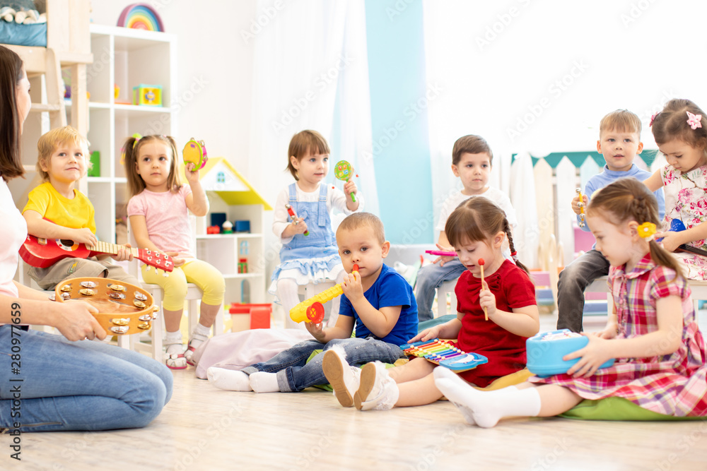 Fototapeta Group of kindergarten children play with musical toys. Early musical education in daycare