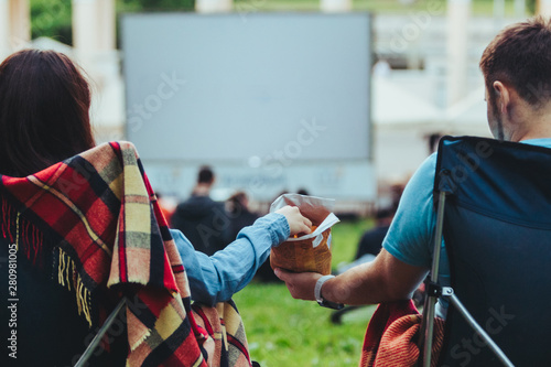 Fotografía couple sitting in camp-chairs in city park looking movie outdoors at open air ci