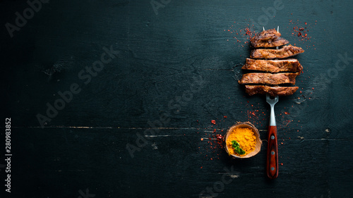 Pork steak on the fork. On a wooden background. Top view. Free space for your text. - 280983852