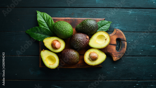 Fotomural Fresh avocado with leaves on a black background