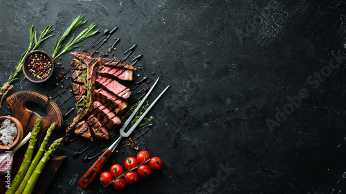 In de dag Steakhouse Beef T-Bone steak on a black table. Top view. Free space for text.