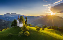 Skofja Loka, Slovenia - Aerial View Of The Beautiful Hilltop Sveti Tomaz (Saint Thomas) Church With A Warm Summer Sunset, Clear Blue Sky And Julian Alps At The Background