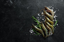 Raw Black Tiger Prawns With Lemon. Seafood. Top View. On A Black Background. Free Copy Space.
