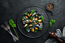 Boiled Mussels With Parsley And Spices On A Black Plate. Top View. Free Space For Your Text.
