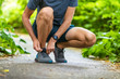 Running shoes sports smartwatch man tying shoe laces. Male fitness runner getting ready to jog in spring autumn jogging outdoor wearing technology wearable smart watch.