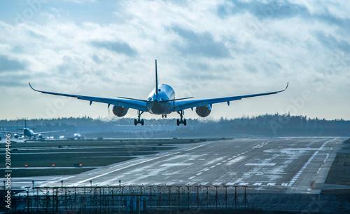 Obraz Airplane landing to airport runway - fototapety do salonu