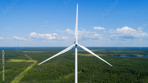 Obraz Wind turbine in summer forest, close up. Colorful aerial landscape. Alternative energy concept. - fototapety do salonu