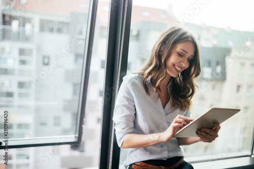 Fotografía  Attractive businesswoman using a digital tablet while standing in front of windo