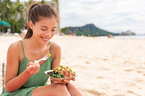 Kobiety łasowania poke puchar ahi tuńczyk na Waikiki plaży Hawaje. Lokalne jedzenie Sałatka rybna wakacje podróż. Azjatyckiej dziewczyny szczęśliwy zdrowy je.