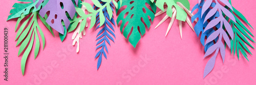 tropical leaves cut from paper on pink background.