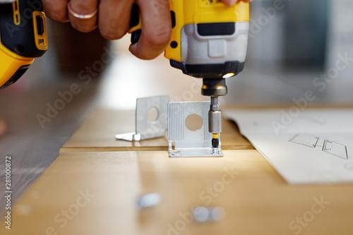 Photo  Man assembling furniture at home using a cordless screwdriver