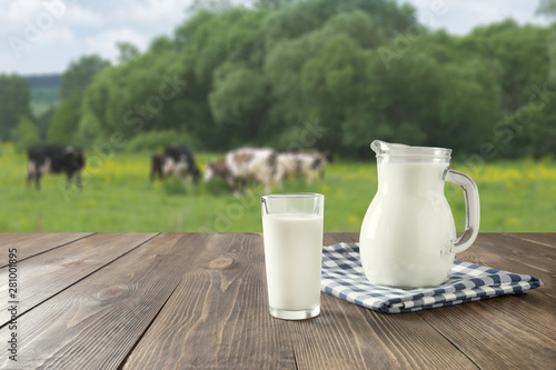 Vászonkép Fresh milk in glass on dark wooden table and blurred landscape with cow on meadow