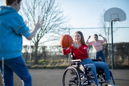 Teenage Girl In Wheelchair Playing Basketball With Friends Wallpaper Mural