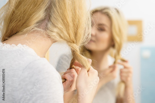 Woman making braid on blonde hair Fototapet