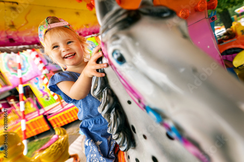 Poster Amusementspark happy smiling little girl sitting on horse carousel at amusement park