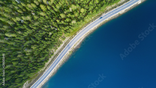 Photo sur Aluminium Bleu nuit Beautiful aerial view of road between green summer forest and blue lake in Lapland. Car moving on road.