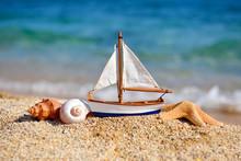 Toy Ship And Seashells On Sand...