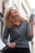 canvas print picture cheerful woman holding mobile phone and looking up