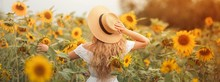 Beautiful Curly Young Woman In A Sunflower Field Holding A Wicker Hat. Portrait Of A Young Woman In The Sun. Summer.