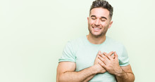 Young Handsome Man Against A Green Background Laughing Keeping Hands On Heart, Concept Of Happiness.