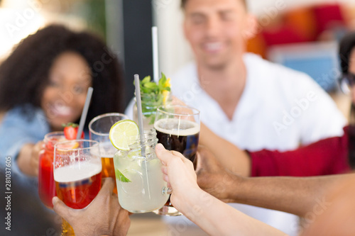Cadres-photo bureau Pain leisure, food and people concept - group of happy international friends clinking glasses at bar or restaurant