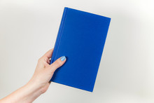 Closeup View Of Female Hand Holding Blue Book With Hardback. Horizontal Color Photography.