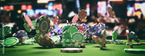 Foto Poker chips falling on green felt roulette table, blur casino interior background