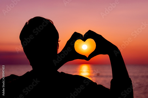 Girls hands in the shape of a heart on the background of the setting sun on the sea.