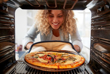 View Looking Out From Inside Oven As Woman Cooks Fresh Pizza
