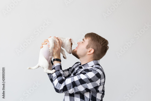 Fototapeta people, pets and animals concept - young man kissing jack russell terrier puppy on white background obraz na płótnie