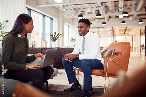 Businesswoman Interviewing Male Job Candidate In Seating Area Of Modern Office Wallpaper Mural