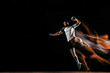 Leinwanddruck Bild - Caucasian young handball player in action and motion in mixed lights over black studio background. Fit male professional sportsman. Concept of sport, movement, energy, dynamic, healthy lifestyle.