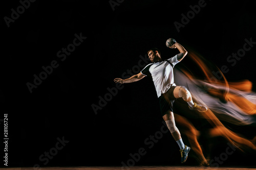 Obraz na plátne Caucasian young handball player in action and motion in mixed lights over black studio background