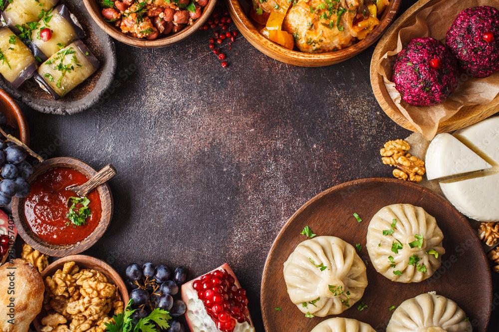 Fototapety, obrazy: Traditional Georgian cuisine background. Khinkali, phali, chahokhbili, lobio, cheese, eggplant rolls, dark background.