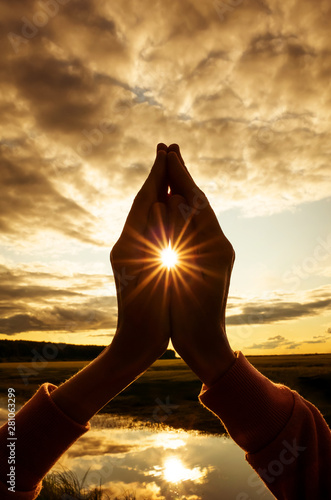 Obraz Tin namaste close-up, the sun shines between the fingers with stunning rays. Silhouette against the setting sun, sky and river. Concept of amateur yoga, healthy lifestyle, meditation practice.  - fototapety do salonu