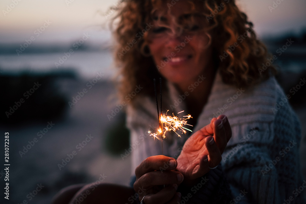Fototapeta New year eve or celebration time for cheerful lady in the evenign night with fire sparklers - focus on fire and defocused portrait in backgrouind - concept of celebration and romance