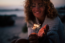 New Year Eve Or Celebration Time For Cheerful Lady In The Evenign Night With Fire Sparklers - Focus On Fire And Defocused Portrait In Backgrouind - Concept Of Celebration And Romance