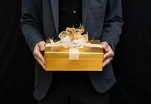 Men In Black Suit Holding Gold Gift Box