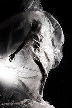 Slim Girl Dressed Only In Underwear Emotionally Posing, Wrapped In Fluttering In The Wind And Fitting Her Graceful Young Body Cellophane Film. Artistic, Creative, Abstract Design. Black And White