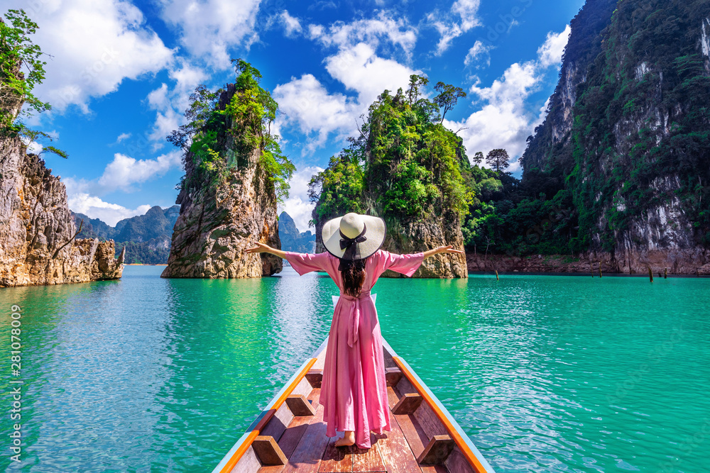 Fototapety, obrazy: Beautiful girl standing on the boat and looking to mountains in Ratchaprapha Dam at Khao Sok National Park, Surat Thani Province, Thailand.