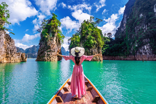 Obraz Beautiful girl standing on the boat and looking to mountains in Ratchaprapha Dam at Khao Sok National Park, Surat Thani Province, Thailand. - fototapety do salonu