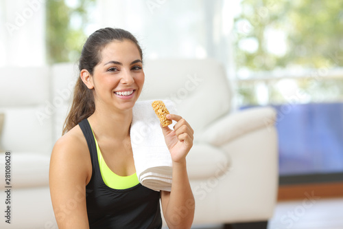 Valokuvatapetti Woman holding an energy bar after sport at home