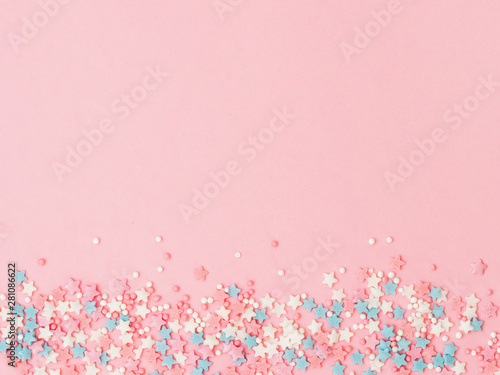 Spoed Fotobehang Bakkerij Festive border frame of colorful pastel sprinkles on pink background, copy space top. Sugar sprinkle dots and stars, decoration for cake and bakery. Top view or flat lay