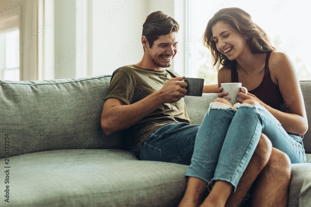 Fototapeta Couple relaxing at home with coffee