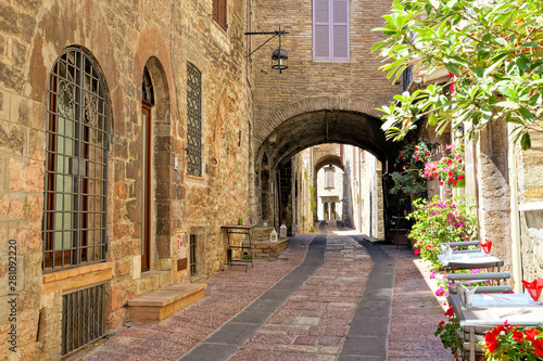 Fototapety, obrazy: Beautiful arched street in the medieval old town of Assisi with flowers and restaurant tables, Italy
