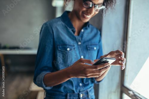 Fotografia  Female entrepreneur using smart phone in office